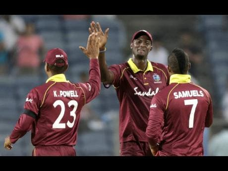 Windies captain Jason Holder (centre) celebrating with Keiron Powell (left) and Marlon Samuels.