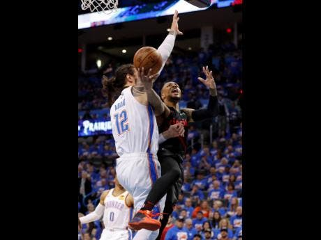 Portland Trail Blazers guard Damian Lillard (0) goes to the basket as Oklahoma City Thunder centre Steven Adams (12) defends in the second half of Game 4 of an NBA basketball first-round playoff series on Sunday.