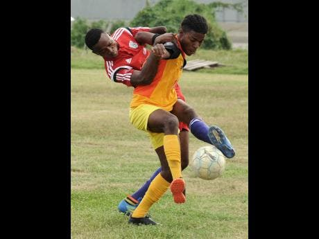 Greenwich Town FC's Shaden Goslin (right) and Olympic Gardens FC's Shakel Grant vie for the ball during a KSAFA/Magnum Major League football match at the Tinson Pen Oval.