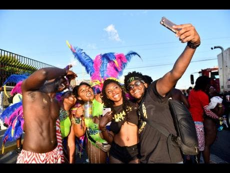 Xaymaca revellers (from left) Jevon Williams, Denille Ashwood, Jamila Samuels, Diamarei Bonner and Shaquiel Brooks take a group photo during yesterday's Road March.