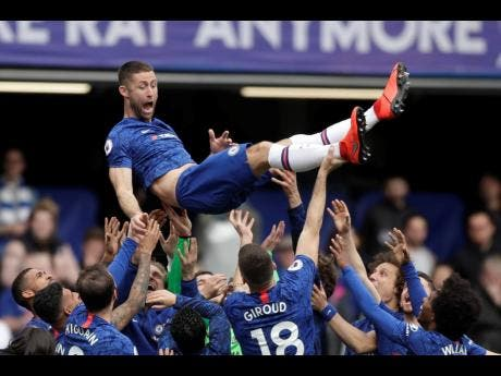 Chelsea's Gary Cahill, (in the air), is cheered by teammates at the end of the English Premier League match between Chelsea and Watford at Stamford Bridge Stadium in London yesterday.