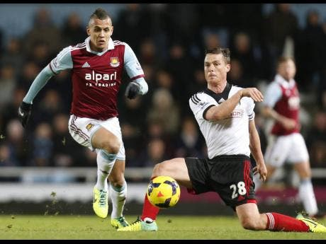 Ravel Morrison (left), then of West Ham United, dribbles by Fulham FC's Scott Parker during an English Premier League game on Saturday, November 30, 2013. Morrison is now having paperwork processed to represent the Jamaica senior men's football team.