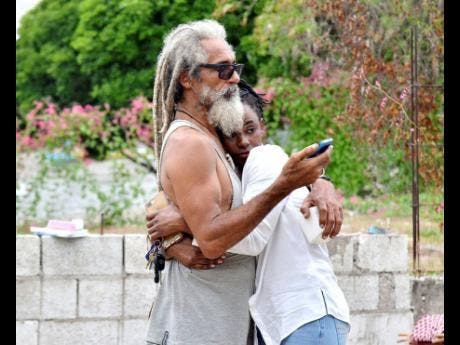 Actor and surfer Billy 'Mystic' Wilmot is comforted by his daughter-in-law, Janice Wilmot, after fire destroyed his home in Nine Miles, Bull Bay, St Andrew, yesterday.