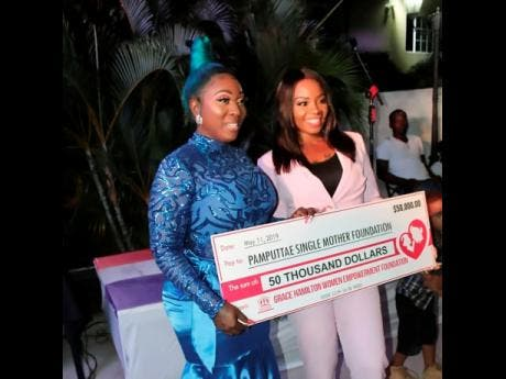 Pamputtae (right) accepts a symbolic cheque of $50,000 from Spice for her Single Mothers Foundation at the launch last Saturday.