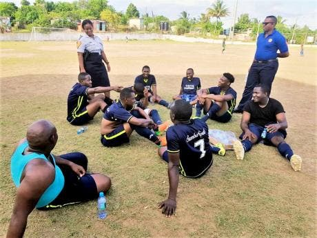 Sergeant Kerry-Ann Maylor Wallace (standing, left) rapping with a group of footballers.