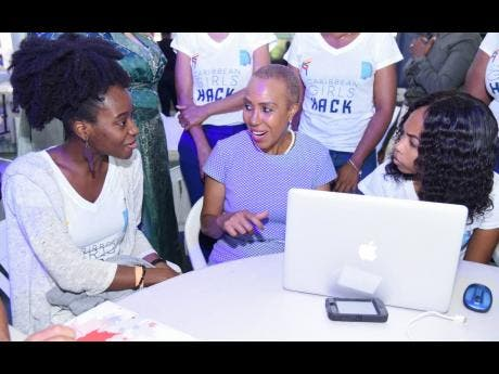 Technology Minister Fayval Williams (centre) engages two participants, Juleen Gentles (left) and Tuwanie Morgan (right), at the opening ceremony for the 2019 Girls Hackathon, held yesterday at the Chinese Benevolent Association in St Andrew.