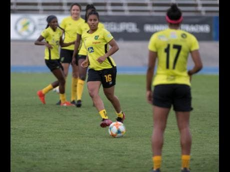 National defender Dominique Bond-Flasza (centre) makes a pass to teammate Allyson Swaby (right) during a training session at the National Stadium on Monday. The Reggae Girlz are preparing for an international friendly against Panama at the same venue on Sunday.
