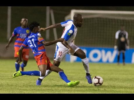 Javon East (right) of Portmore united is tackled by Judlin Piergile of AS Capoise during their FLOW Concacaf Caribbean Club Championhsip match at Stadium East in Kingston last night.