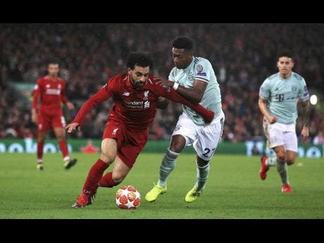 Liverpool's Mohamed Salah (left) and Bayern Munich's David Alaba battle for the ball, during their first leg UEFA Champions League round-of-16 match at Anfield, in Liverpool, England, on Tuesday, February 19.