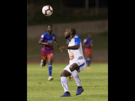 Portmore United's Javon East prepares to cushion a header during the FLOW Concacaf Club Championship game against Haitian side AS Capoise at Stadium East on Tuesday night.