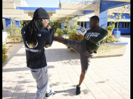 Imran Hall (right) spars with Mixed Martial Arts Jamaica Sport president Cleon Bardowell.
