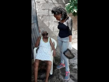 Sonika Tracey (right) chats with Dollice Dear as her schoolmates clean up the elderly woman's home.