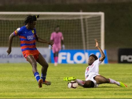 Frantz Moise (left) of AS Capoise loses possession to Denilson Pierre of Real Hope FA, who put in a solid sliding tackle during their FLOW Concacaf Caribbean Club Championship game at Stadium East yesterday.