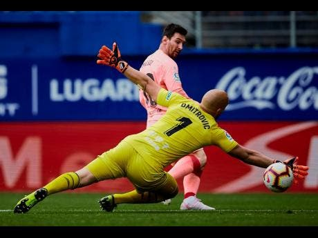 Barcelona's Lionel Messi shoots to score in front of Eibar's goalkeeper Marko Dmitrovic, during a Spanish La Liga match at the Ipurua stadium in Eibar, northern Spain, yesterday.