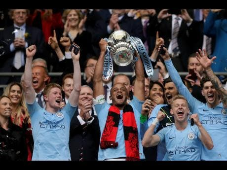 Manchester City's team captain Vincent Kompany lifts the trophy after winning the English FA Cup Final between Manchester City and Watford at Wembley Stadium in London on Saturday, May 18.