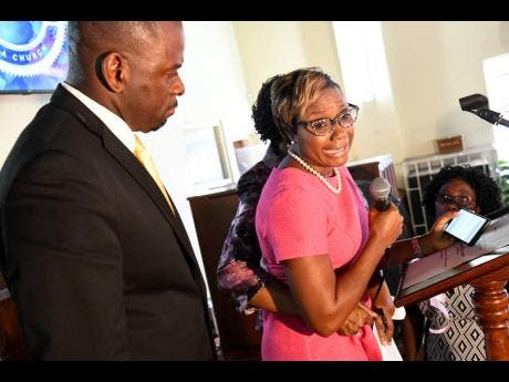 Pastor Leslie Pinnock assists Member of Parliament Juliet Cuthbert- Flynn as she broke down during her tribute.