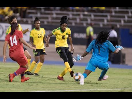 Reggae Girl Shakira Duncan (second from right) scores Jamaica's third goal against Panama yesterday at the National Stadium.