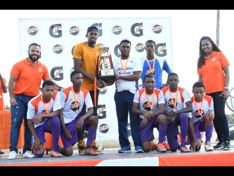 Kingston College's Five-A-Side team (all crouched) and coach Raymond Watson (centre) collect their trophy from brand ambassador Usain Bolt (fourth left) after capturing the Gatorade 5v5 Football tournament with a 2-0 win over Excelsior High School at the Barbican Field on Sunday, March 10.