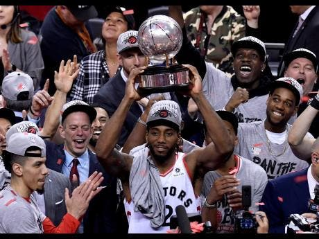 Toronto Raptors forward Kawhi Leonard (2) holds up the trophy after the team's 100-94 win over the Milwaukee Bucks in Game 6 of the NBA basketball playoffs Eastern Conference finals on Saturday, May 25, 2019, in Toronto. The Raptors advanced to the NBA Finals.