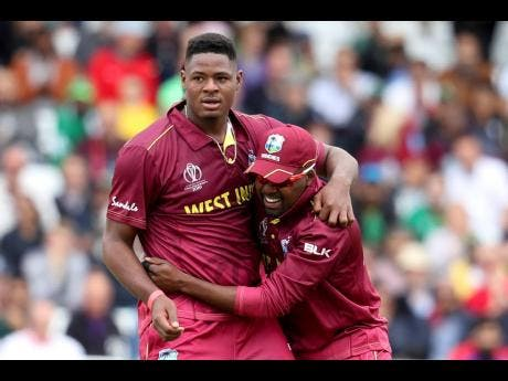 West Indies bowler Oshane Thomas is embraced by teammate Darren Bravo after he dismissed Pakistan's Shadab Khan during their Cricket World Cup match at Trent Bridge cricket ground in Nottingham, England, last Friday.