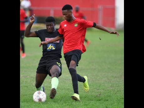 Jermaine Reid of Molynes United makes a challenge on  Lime Hall player Shaquill Wallace  in the JFF Premier league play-off at the  Constant Spring playing field on Sunday.