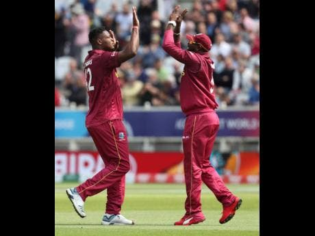 West Indies' Oshane Thomas (left), celebrates with West Indies' Ashley Nurse after bowling Australia's captain Aaron Finch, caught West Indies' Shai Hope during the Cricket World Cup match between Australia and West Indies at Trent Bridge in Nottingham on Thursday, June 6.