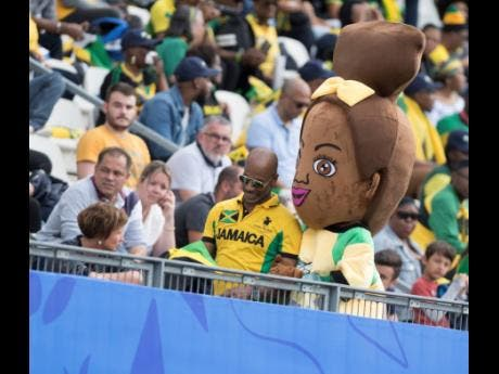 Reggae Girlz Mascot Toya strike a pose with a fan in the stands at the Jamaica vs Brazil match in the 2019 FIFA Women's World Cup at the Stade des Alpes in Grenoble, France, yesterday.