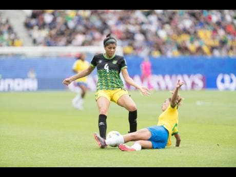 Chantelle Swaby (left) of Jamaica is challeneged by Brazil's Tamires Dias De Britto in Jamaica's opening match against the South Americans at the 2019 FIFA Women's World Cup at the Stade des Alpes in Grenoble, France.