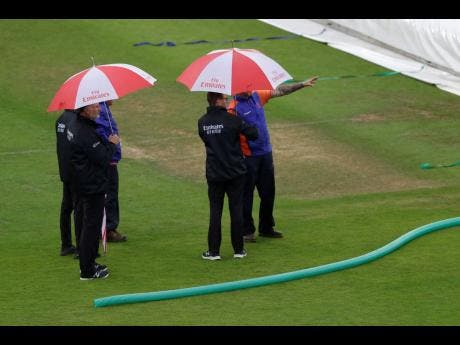Umpires inspect the pitch after rain stopped play during the ICC World Cup cricket match between South Africa and the West Indies at the Ageas Bowl in Southampton yesterday.