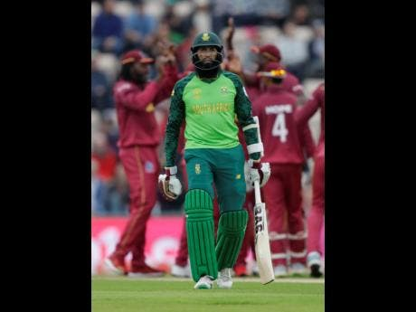 South Africa's Hashim Amla leaves the pitch after he is caught by West Indies' Chris Gayle off the bowling of West Indies' Sheldon Cottrell.