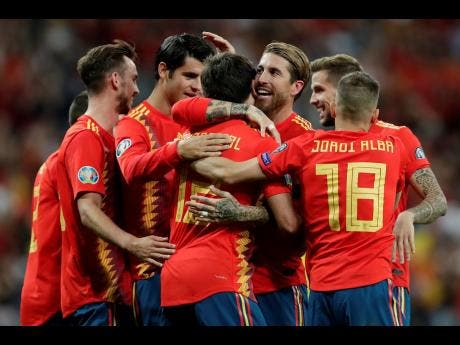 Spain's Mikel Oyarzabal (centre front) celebrates with teammates after scoring his side's third goal during the Euro 2020 Group F qualifying match between Spain and Sweden at the Santiago Bernabeu stadium in Madrid yesterday.