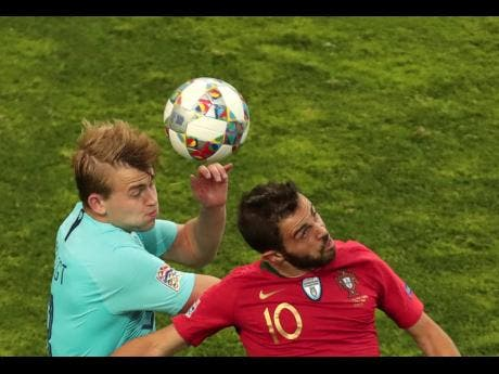 Portugal's Bernardo Silva (right) jumps for the ball with Netherlands' Matthijs de Ligt during the UEFA Nations League final match between Portugal and Netherlands at the Dragao stadium in Porto, Portugal, on Sunday.