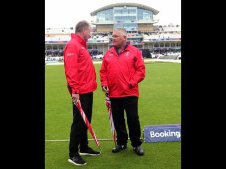 Umpires Paul Ronald Reiffel of Australia (left) with Marais Erasmus of South Africa walk off the field after inspecting the ground as the rain delays start of the Cricket World Cup match between India and New Zealand at Trent Bridge in Nottingham yesterday.