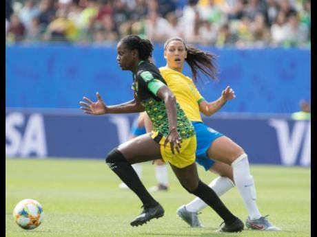 Reggae Girlz team captain Konya Plummer (left) dribbles by Brazil's Beatriz Zaneratto Joao in the Jamaica's opening game of the 2019 FIFA Women's World Cup against Brazil on June 9, 2019.