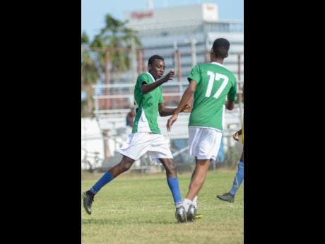 Tivoli Gardens' Under-17 player Junior Walker (left) celebrates with teammate Jalon Blair after scoring Tivoli's third goal  against Santos  during the Edward Seaga Sports Festival at the Edward Seaga Sports Complex in the western Kingston community yesterday.