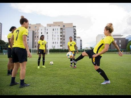 Allyson Swaby (obscured), Chinyelu Asher, Olufolasade Adamolekun, Dominique Bond-Flasza, and Ashleigh Shimm juggle the ball in a training session, yesterday at Stade Eugene Thenard in Grenoble, France.