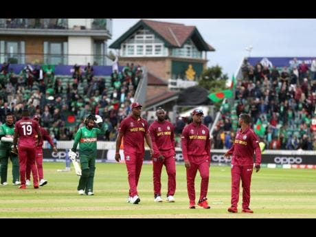 West Indies players walk off dejected after losing the Cricket World Cup match between West Indies and Bangladesh at The Taunton County Ground, Taunton, south west England, yesterday.