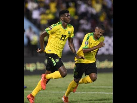 Damion Lowe and Leon Bailey celebrate after Lowe scored a header to put Jamaica up 3-1 in the 56th minute.