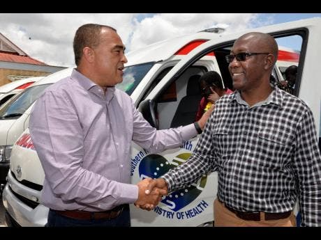 Health and Wellness Minister Dr Christopher Tufton (left) greets Robert Robinson, transport coordinator for the Southern Regional Health Authority.
