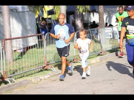 A father and a daughter participate in the Fathers and Children 3K run.