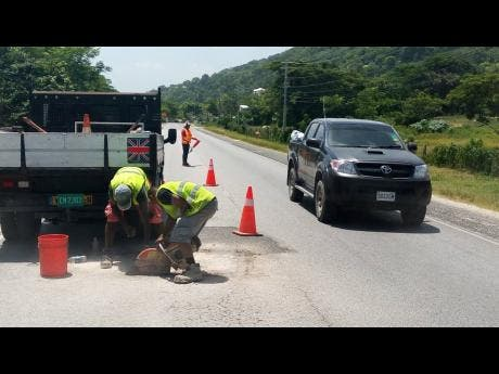 Several workmen contracted to the National Works Agency carry out repair work yesterday on the section of roadway in Barbican, Hanover where popular Lucea bus operator Everton 'Wanga' Riley, and Kevaughn Sutherland lost their lives in a motor vehicle accident, on Wednesday.