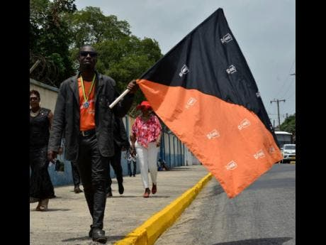 Rohan Banner carries a flag which represents the Tivoli Gardens Football Club as he attends the state funeral of the former Club President and Prime Minister Edward Seaga yesterday.