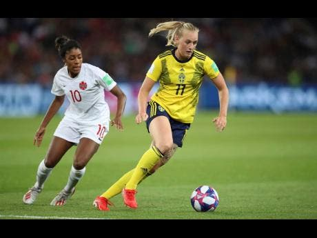 Sweden's Stina Blackstenius is being chased by Canada's Ashley Lawrence during the Women's World Cup round-of-16 match at Parc des Princes in Paris, France, yesterday. Sweden won 1-0.