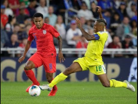 United States' Weston McKennie (8) tries to keep the ball from Guyana's Neil Danns (16) during the second half of a CONCACAF Gold Cup match yesterday.