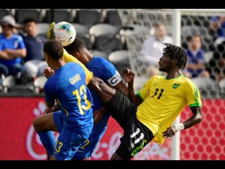 Jamaica forward Shamar Nicholson (right) kicks between Curacao defenders Jurien Gaari (left) and Cuco Martina during the first half of a Concacaf Gold Cup match yesterday.