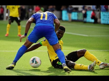 Curacao forward Gevaro Nepomuceno (left) and Jamaica defender Kemar Lawrence compete for the ball during the first half of a Concacaf  Gold Cup match yesterday. The Reggae Boyz gave up a late goal to draw the contest 1-1.