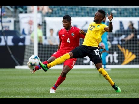 Panama's Fidel Escobar (left) and Jamaica's Junior Flemmings battle for the ball during the first half of a Concacaf Gold Cup match on Sunday in Philadelphia. Jamaica won 1-0 to progress to the semi-finals.