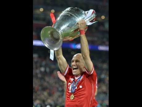 In this May 25, 2013 file photo, Bayern Munich's Arjen Robben of the Netherlands lifts the trophy after winning the Champions League final against Borussia Dortmund.