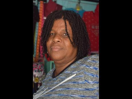 Sheryl Richardson recalls Chris Gayle's contribution to the Rollington Town community at her place of business on Jackson Road yesterday.
