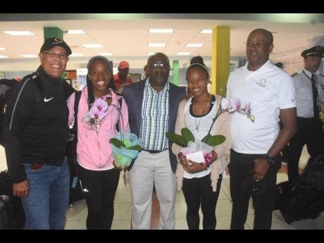 Match officials Princess Brown (second left) and Stephanie-Dale Yee Sing (second right) are greeted by FIFA referee instructor Peter Prendergast (left), Jamaica Football Federation (JFF) general secretary Dalton Wint (centre) and JFF Referees Department manager Victor Stewart on arrival at the Norman Manley International Airport in Kingston last night. The duo were returning from their duty as assistant referees at the just concluded FIFA Women's World Cup in France. Contributed